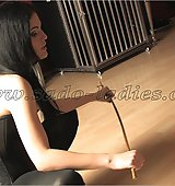 Black haired goddess gives a slave a hard caning.