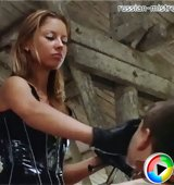 Young blonde mistress in a black latex outfit tortures her naked slave at an old run-down barn